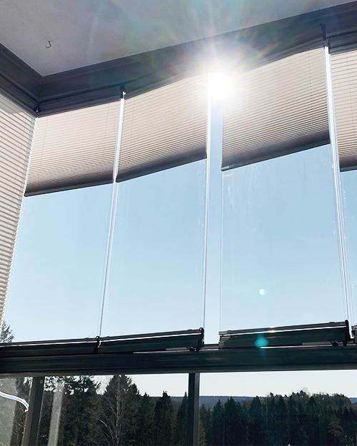 Morris Interiör har monterat plisségardiner som solskydd på en inglasad balkong